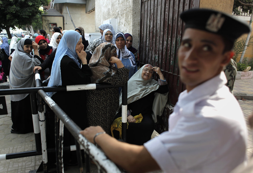 Photo -   An Egyptian policeman stands guard as women lineup outside a polling station during the second day of voting in the presidential runoff election in Cairo, Egypt, Sunday, June 17, 2012. Egyptians are choosing between a conservative Islamist and Hosni Mubarak's ex-prime minister in a second day of a presidential runoff that has been overshadowed by the domination of the country's military. (AP Photo/Nasser Nasser)