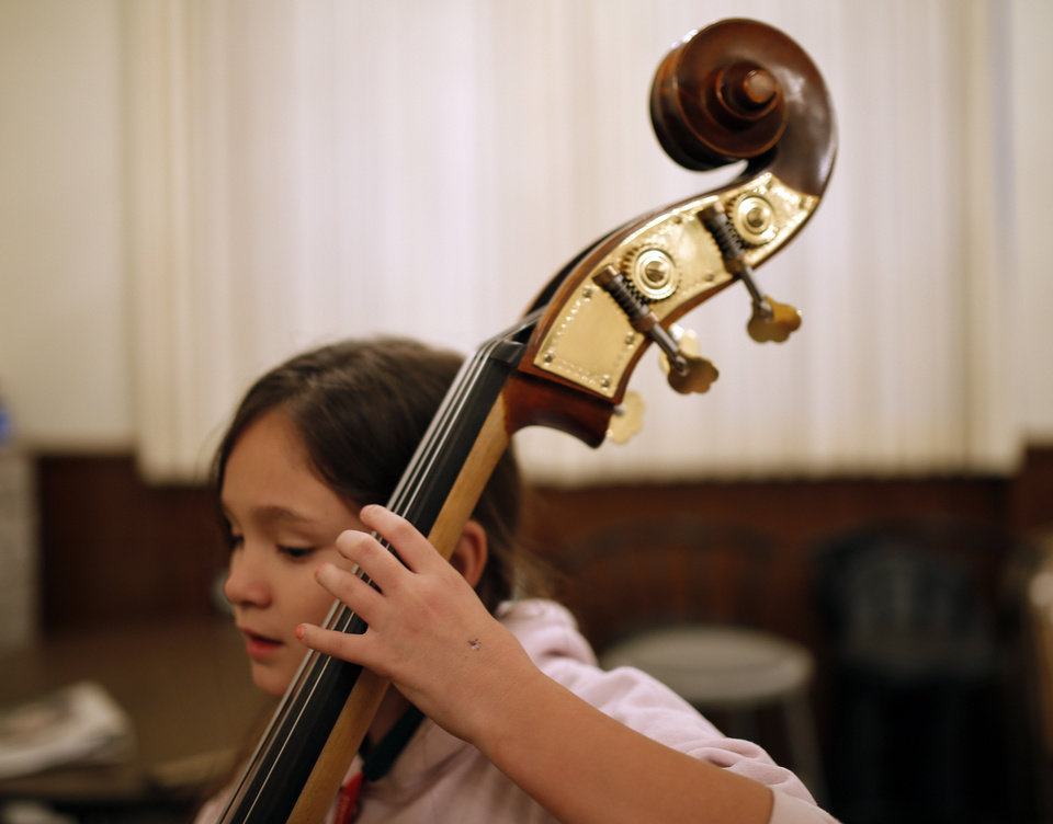 Photo - Gatewood Elementary School fourth-grader Izzabella (CQ) Truong-Richardson, 9, practices on a bass during a recent El Sistema Oklahoma session.  SARAH PHIPPS - The Oklahoman
