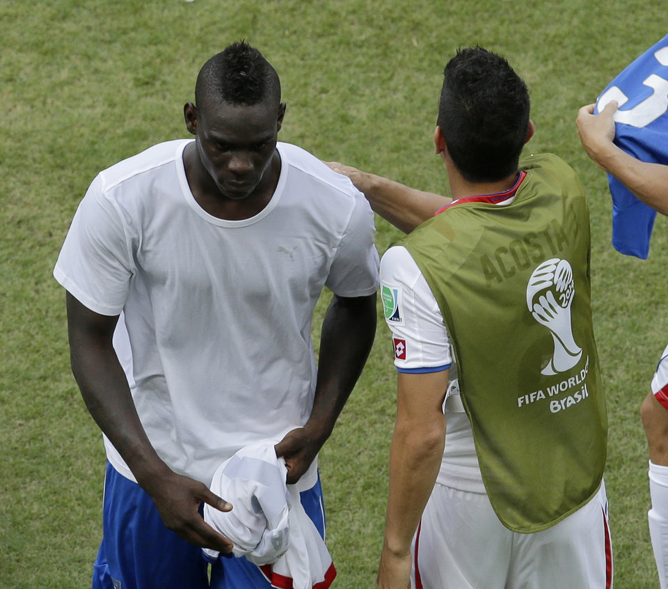 Photo - Italy's Mario Balotelli, left, leaves the pitch after the group D World Cup soccer match between Italy and Costa Rica at the Arena Pernambuco in Recife, Brazil, Friday, June 20, 2014. Costa Rica beat four-time champion Italy 1-0 to secure a spot in the next round. (AP Photo/Hassan Ammar)