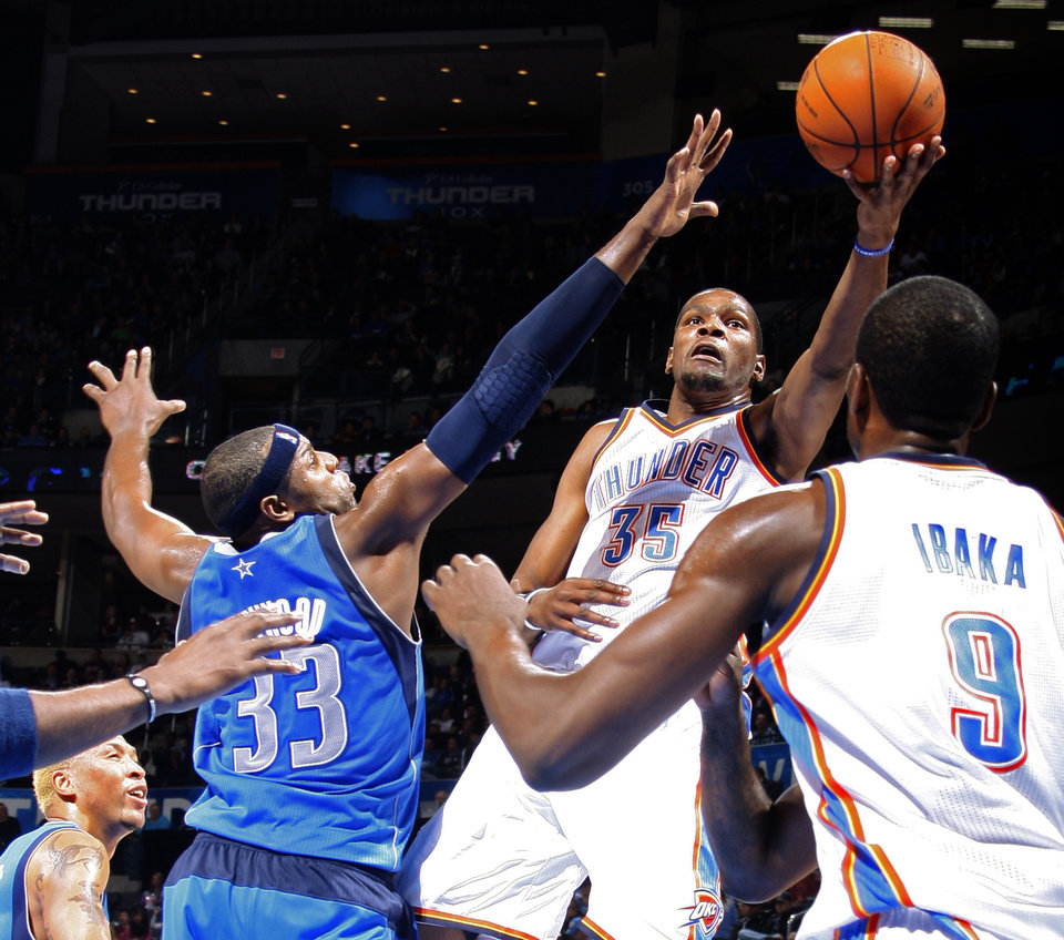 Photo - Oklahoma City's' Kevin Durant (35) goes past Dallas' Brendan Haywood (33) during a preseason NBA game between the Oklahoma City Thunder and the Dallas Mavericks at Chesapeake Energy Arena in Oklahoma City, Tuesday, Dec. 20, 2011. Photo by Bryan Terry, The Oklahoman
