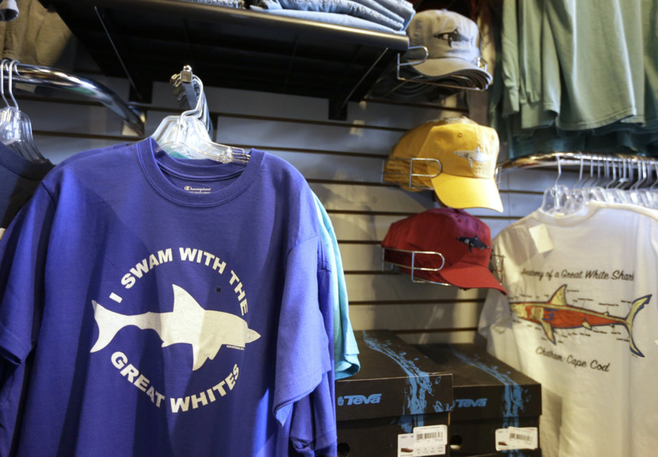 Photo - In this July 2, 2014 photo, shark-themed clothing is on display at the Chatham Clothing Bar in Chatham, Mass. Growing sightings of great white sharks off Cape Cod are generating business for local entrepreneurs as residents and tourists seek a glimpse of the offshore predators -- or purchase their shark-themed memorabilia and apparel. (AP Photo/Steven Senne)