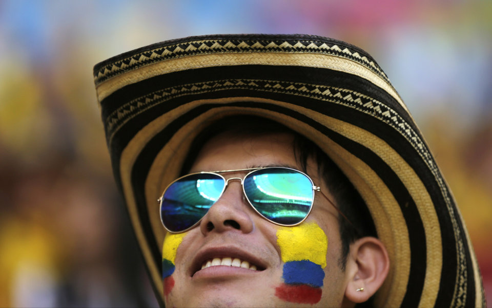 A Columbian fan has the stands in the Estadio Nacional reflected in his sunglasses before the group C World Cup soccer match between Colombia and Ivory Coast at the Estadio Nacional in Brasilia, Brazil, Thursday, June 19, 2014.  (AP Photo/Fernando Llano)