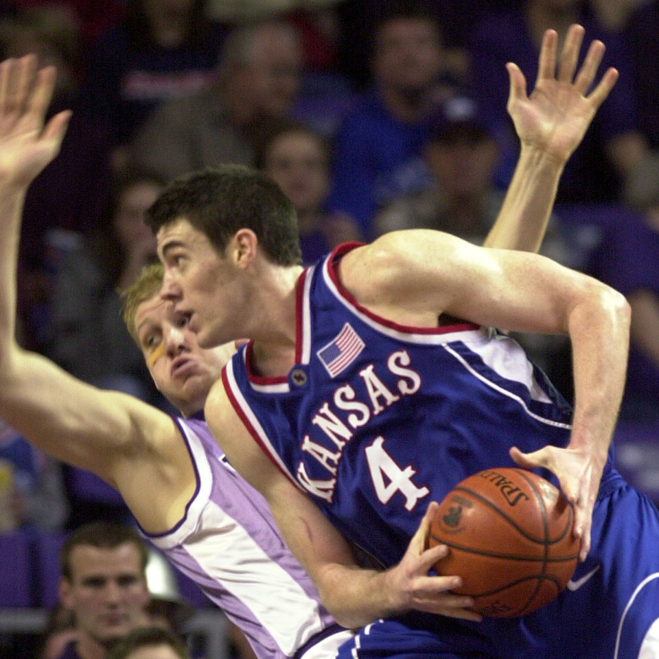 Photo - COLLEGE BASKETBALL: Kansas forward Nick Collison (4) fouls Kansas State forward Travis Canby as he drives to the basket during the second half Saturday, Feb. 8, 2003 in Manhattan, Kan. Kansas won the game 82-64. (AP Photo/Charlie Riedel)