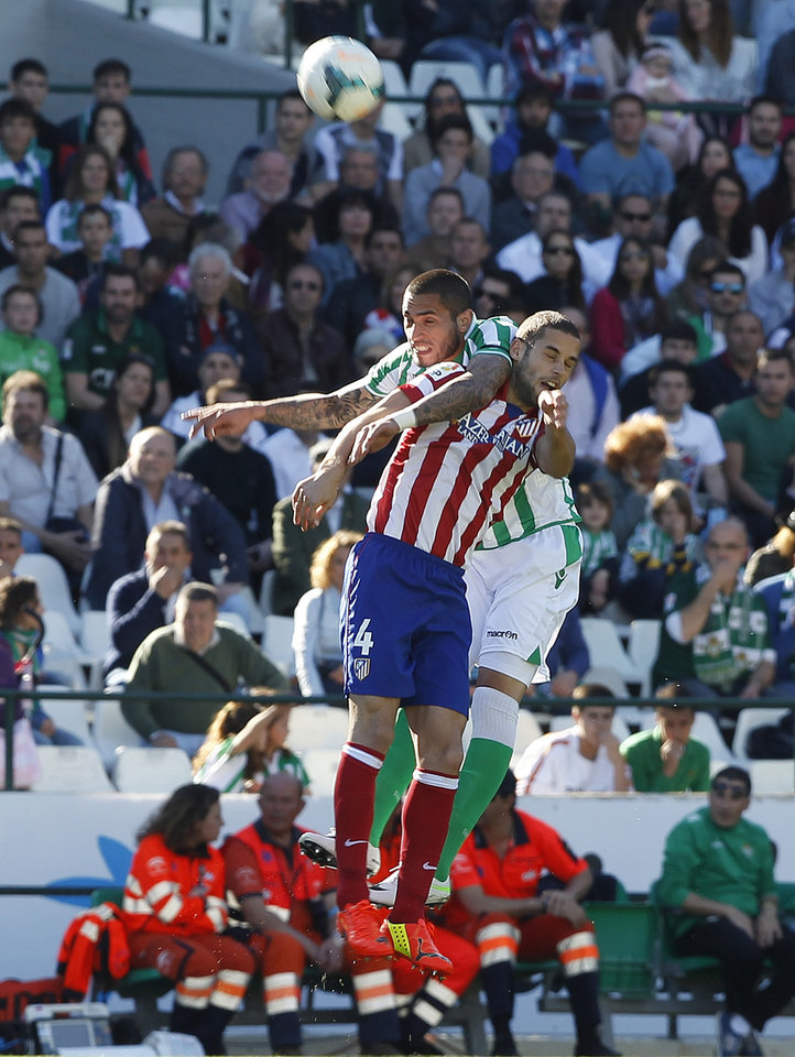 Photo - Atletico de Madrid's Mario Suarez, front, and Betis' Braian Rodriguez, behind, fight for the ball during their La Liga soccer match at the Benito Villamarin stadium, in Seville, Spain on Sunday, March 23, 2014. (AP Photo/Angel Fernandez)