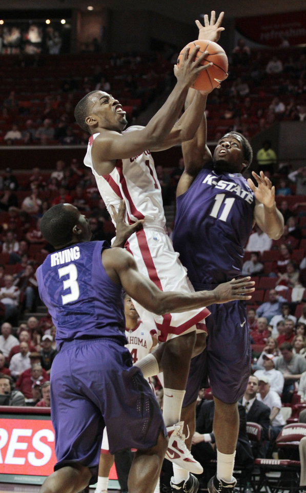 Photo - Oklahoma Sooners' Sam Grooms (1) shoots over Kansas State Wildcats' Martavious Irving (3) and Nino Williams in the second half as the University of Oklahoma (OU) Sooners defeat the Kansas State Wildcats 82-73 in men's college basketball at the Lloyd Noble Center on Saturday, Jan. 14, 2012, in Norman, Okla.  Photo by Steve Sisney, The Oklahoman