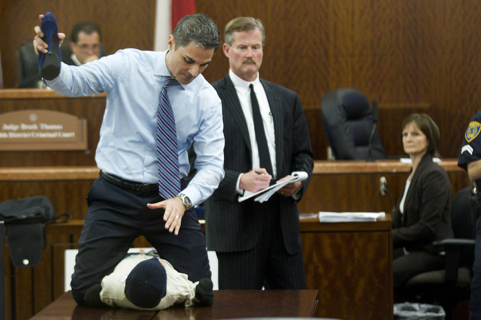 Photo - Prosecutor John Jordan does a crime scene demonstration, using a dummy, during the trial against Ana Trujillo  Tuesday, April 1, 2014, in Houston. Trujillo, 45, is charged with murder, accused of killing her 59-year-old boyfriend, Alf Stefan Andersson with the heel of a stiletto shoe, at his condominium in June 2013. Defense attorney Jack Carroll, center, and crime scene investigator Christopher Duncan are shown in the background. (AP Photo/Houston Chronicle, Brett Coomer ) MANDATORY CREDIT.