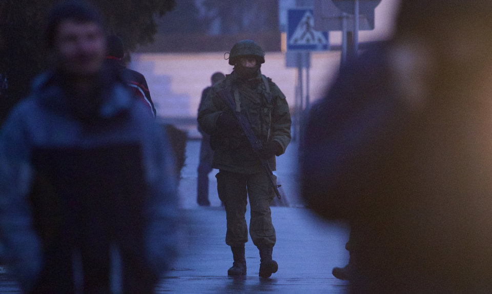 Photo - An unidentified armed man patrols a square in front of the airport in Simferopol, Ukraine, Friday, Feb. 28, 2014.  Dozens of armed men in military uniforms without markings occupied the airport in the capital of Ukraine's strategic Crimea region. (AP Photo/Ivan Sekretarev)