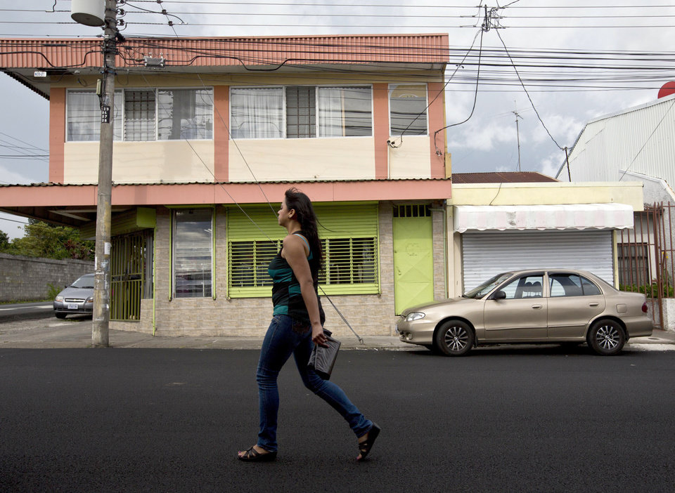 Photo - In this July 9, 2014 photo, a woman walks in front of the building that once housed the human rights group Fundacion Operacion Gaya Internacional in Heredia, Costa Rica. Fernando Murillo was the charismatic head of the group and he'd been contracted by Creative Associates to turn Cuba's politically apathetic young people into