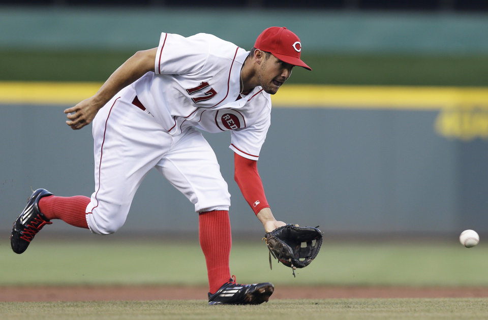 Photo - Cincinnati Reds third baseman Kris Negron fields a ground ball hit by Chicago Cubs' Starlin Castro in the first inning of a baseball game, Wednesday, Aug. 27, 2014, in Cincinnati.Negron threw Castro out at first. (AP Photo/Al Behrman)