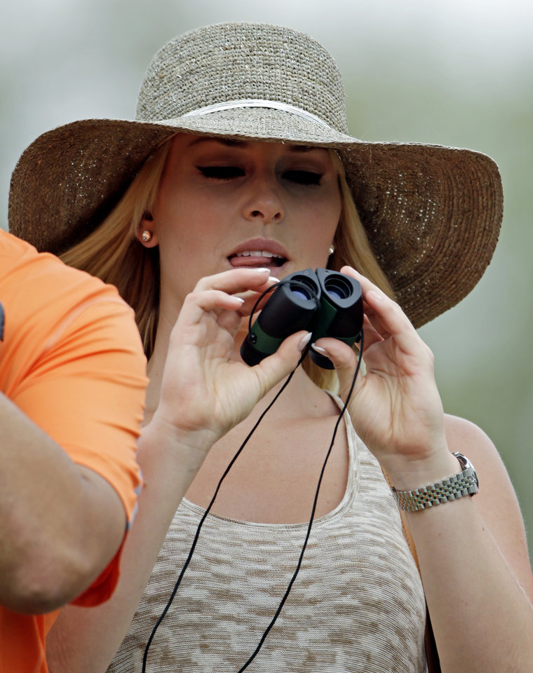 Photo - Skier Lindsey Vonn tries a pair binoculars to watch Tiger Woods during the first round of the Masters golf tournament Thursday, April 11, 2013, in Augusta, Ga. (AP Photo/Darron Cummings)