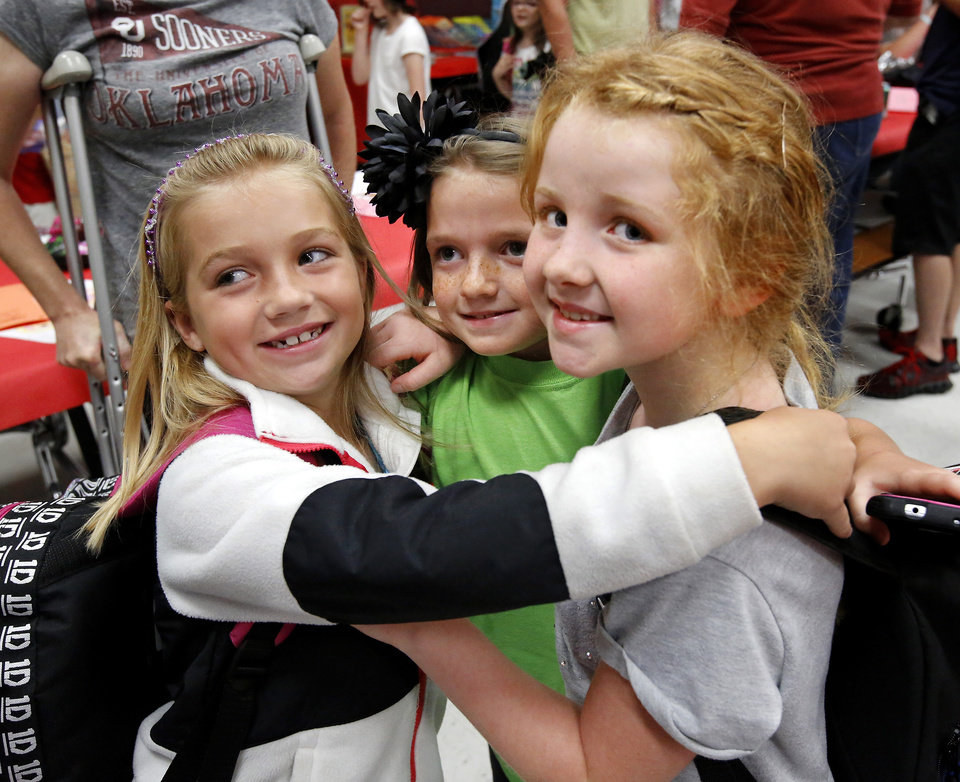 These second grade friends huddle together to pose for a picture taken by one of their parents. From left, Brylee Fanning, Hannah Osborne and Brie Harlow. There was lots of hugging and plenty of joy at Eastlake Elementary School on SW 134, when Eastlake School hosted a reunion of students, parents, teachers and families from Plaza Towers Elementary School on Thursday, May 23, 2013. Seven students died at Plaza Towers School in Monday\'s EF-5 tornado, which also destroyed the school. Photo by Jim Beckel, The Oklahoman.