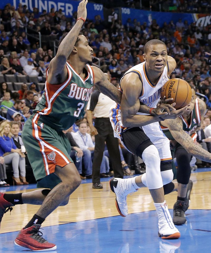 Photo - Oklahoma City's Russell Westbrook (0) drives past Milwaukee 's Brandon Jennings (3) during the season finally NBA basketball game between the Oklahoma City Thunder and the Milwaukee Bucks at Chesapeake Energy Arena on Wednesday, April 17, 2013, in Oklahoma City, Okla.   Photo by Chris Landsberger, The Oklahoman