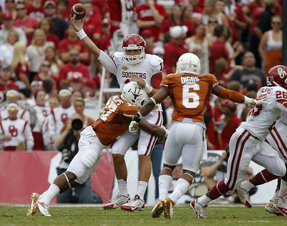 OU's Blake Bell (10) is hit by UT's Adrian Phillips (17) as he throws an interception that was returned for a touchdown during the Red River Rivalry college football game between the University of Oklahoma Sooners and the University of Texas Longhorns at the Cotton Bowl Stadium in Dallas, Saturday, Oct. 12, 2013. Photo by Bryan Terry, The Oklahoman