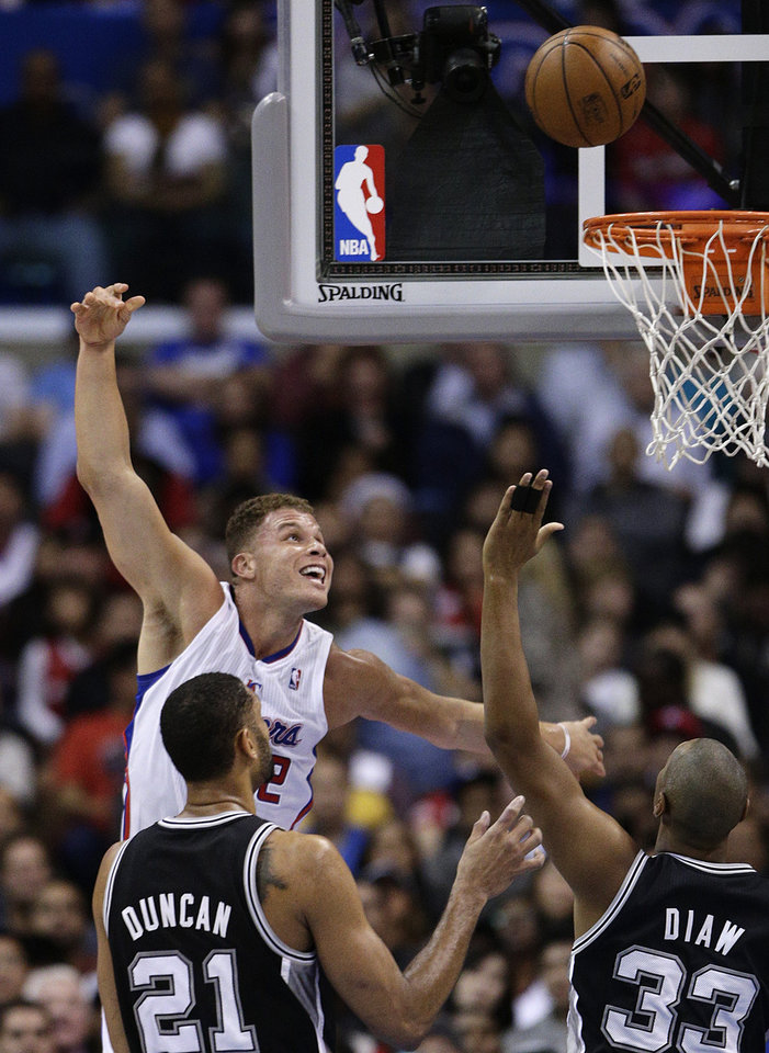 Los Angeles Clippers' Blake Griffin, top left, puts up a shot as San Antonio Spurs' Tim Duncan, bottom left, and Boris Diaw watch during the first half of an NBA basketball game on Monday, Dec. 16, 2013, in Los Angeles. (AP Photo/Jae C. Hong)