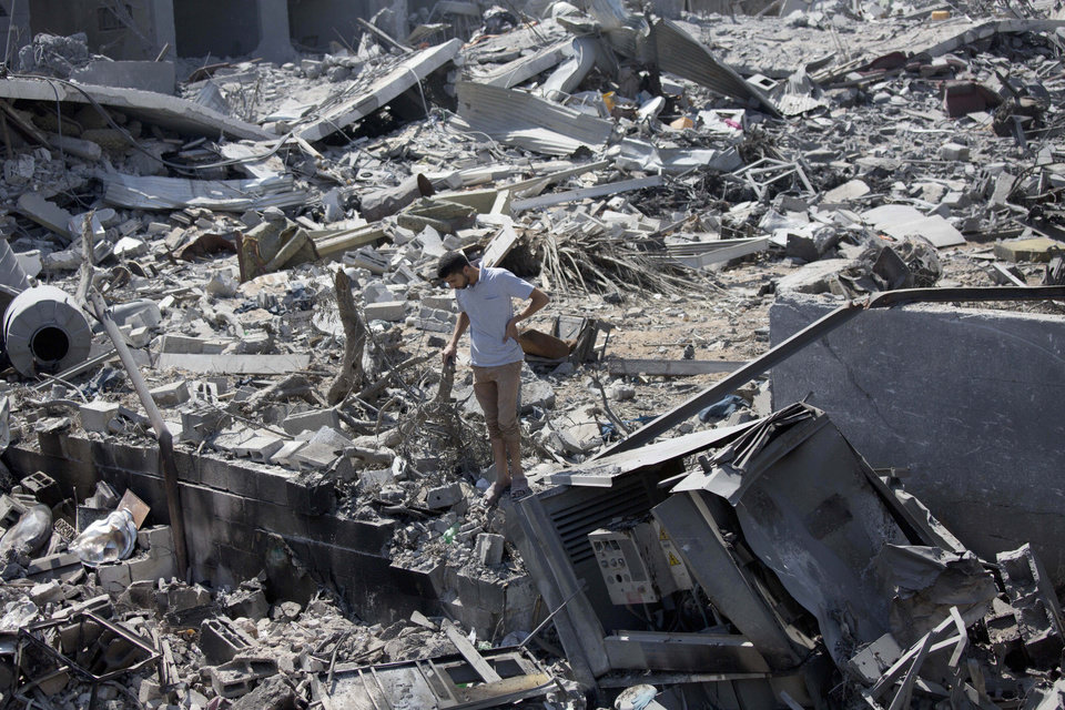 Photo - A Palestinian inspects a destroyed house in the heavily bombed Gaza City neighborhood of Shijaiyah, close to the Israeli border, Friday, Aug. 1, 2014. A three-day Gaza cease-fire that began Friday quickly unraveled, with Israel and Hamas accusing each other of violating the truce. (AP Photo/Dusan Vranic)