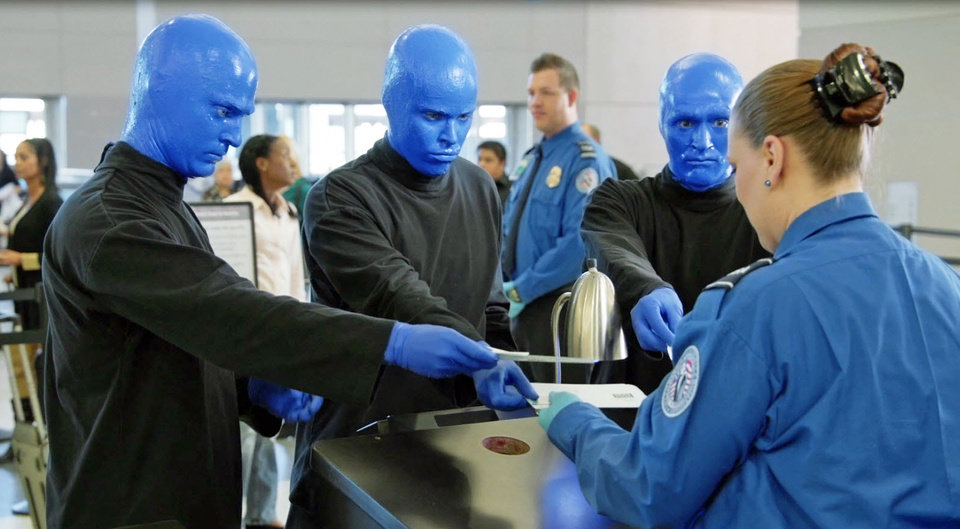 Photo - In this frame from video provided by R&R Partners released in May 2014, Las Vegas performers Blue Man Group present documents to a Transportation Security Administration official in one of eight funny videos that play at security checkpoints at Las Vegas' McCarran International Airport. Tourism officials released the humorous new videos illustrating TSA policies as travelers wait for screenings. Other videos feature Las Vegas comedians Carrot Top, Louie Anderson, ventriloquist Terry Fator, among others. They address TSA procedures for liquids, gels and aerosols, metals and electronics, carry-on luggage, strollers, weapons and more. (AP Photo/R&R Partners)