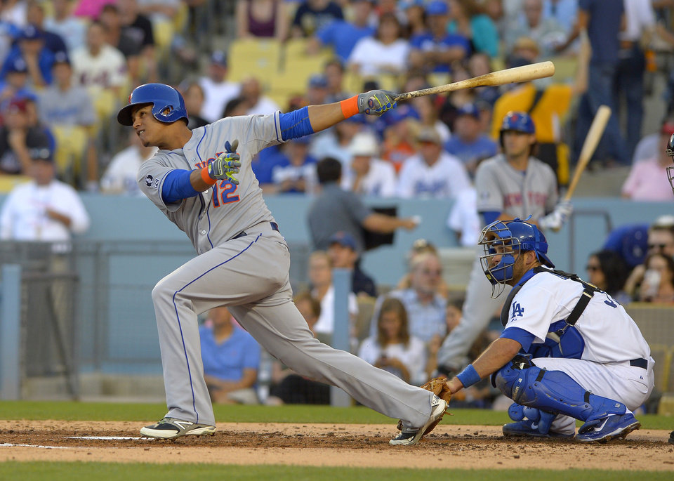 Photo - New York Mets' Juan Lagares follows through on a three-run home run in front of Los Angeles Dodgers catcher Drew Butera during the fourth inning of a baseball game, Saturday, Aug. 23, 2014, in Los Angeles. (AP Photo/Mark J. Terrill)