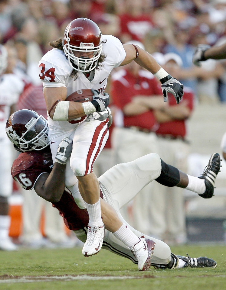 Photo - OU's Matt Clapp fights off Mat Featherston of Texas A&M in the second half during the college football game between the University of Oklahoma and Texas A&M University at Kyle Field in College Station, Texas, Saturday, November 8, 2008.  BY BRYAN TERRY, THE OKLAHOMAN