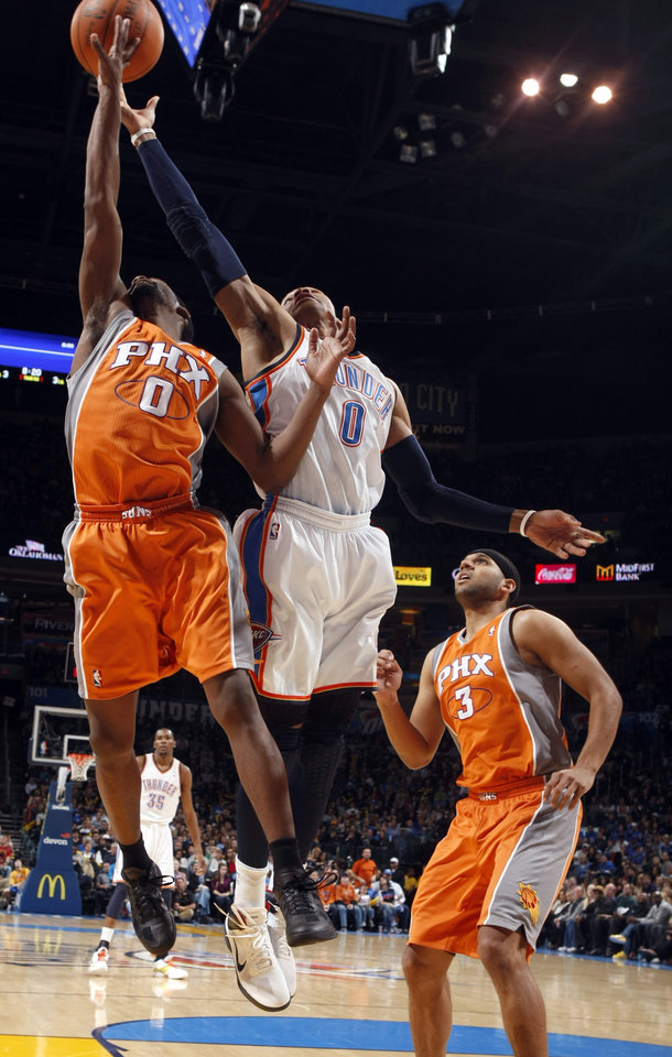 Photo - Oklahoma City's Russell Westbrook (0) and Phoenix's Aaron Brooks (0) fight for a rebound as Phoenix's Jared Dudley (3) looks on during the NBA game between the Oklahoma City Thunder and the Phoenix Suns, Sunday, March 6, 2011, the Oklahoma City Arena. Photo by Sarah Phipps, The Oklahoman.