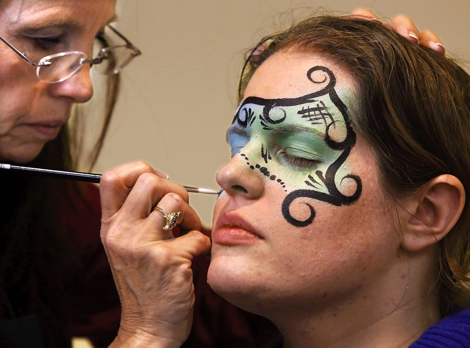 Emily Hunt, a circulation librarian, has a colorful design painted on her face by