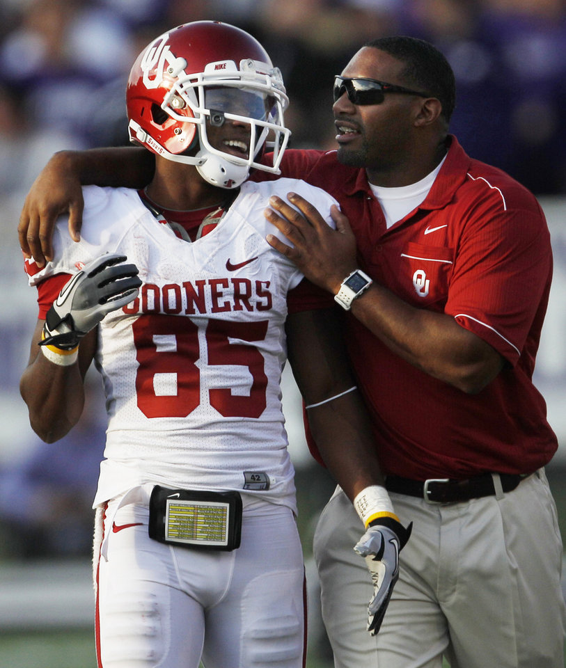 Photo - Oklahoma wide receiver Ryan Broyles (85) is congratulated by assistant coach Cory Callens, right, during the second half of an NCAA college football game against Kansas State Saturday, Oct. 29, 2011, in Manhattan, Kan. Broyles caught 14 passes for 171 yards. Oklahoma defeated Kansas State 58-17. (AP Photo/Orlin Wagner) ORG XMIT: KSOW118