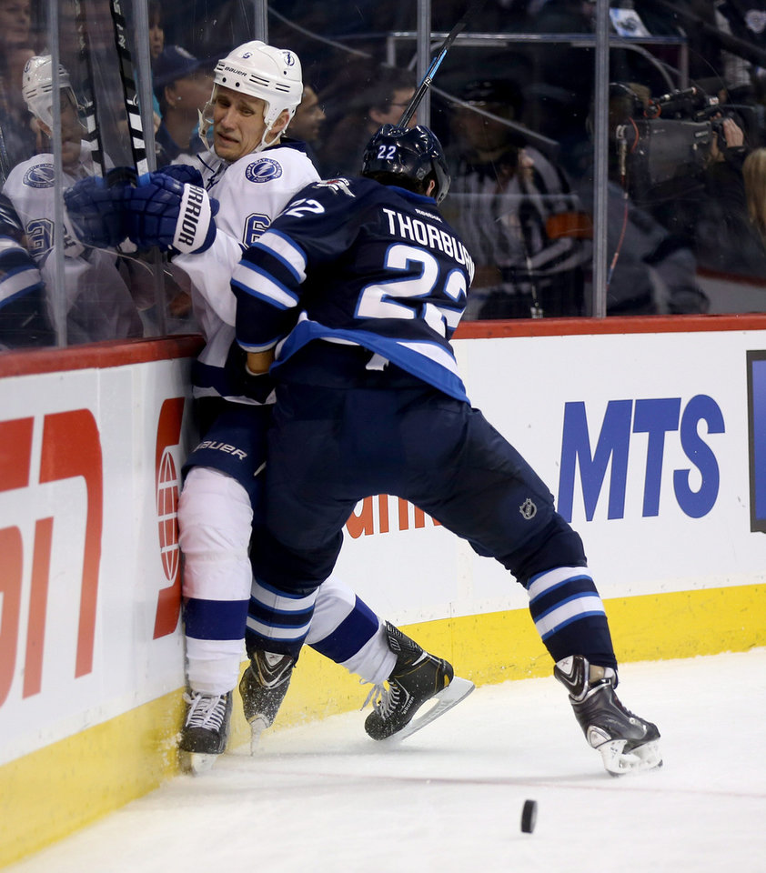 Photo - Tampa Bay Lightning's Sami Salo (6) is slammed into the boards by Winnipeg Jets' Chris Thorburn (22) during the second period of an NHL hockey game Tuesday, Jan. 7, 2014, in Winnipeg, Manitoba. (AP Photo/The Canadian Press, Trevor Hagan)