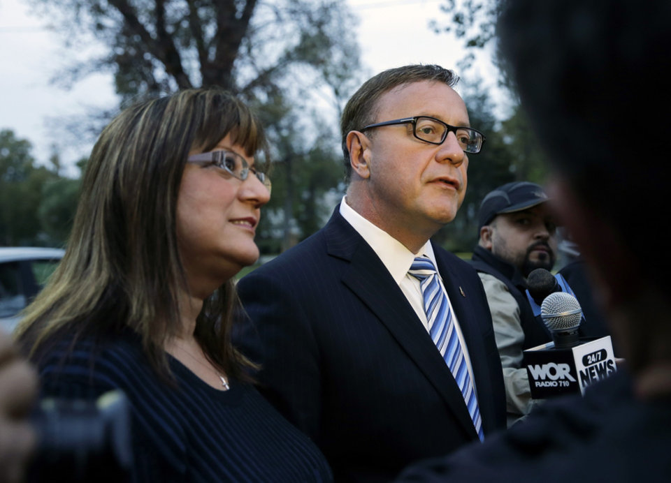 Photo - As his wife, Lorraine Rossi Lonegan, left, stands nearby, Republican senate candidate Steve Lonegan answers a question after voting in Bogota, N.J., Wednesday, Oct. 16, 2013. Lonegan and Democrat Cory Booker are vying to fill the Senate seat left vacant by the death of Frank Lautenberg. (AP Photo/Mel Evans)