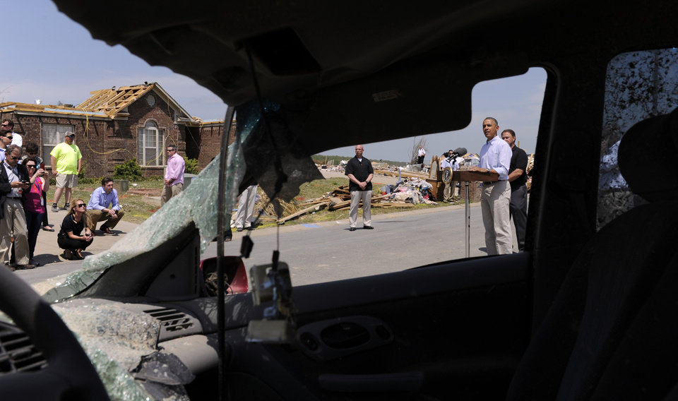 Photo - Framed by a damaged car, President Barack Obama speaks after touring tornado-damaged neighborhood of Vilonia, Ark., Wednesday, May 7, 2014. Obama is visiting with first responders and families affected by the recent tornados before traveling on to California where he will raise money for the Democratic Party and receive an award from a foundation created by movie director Steven Spielberg. (AP Photo/Susan Walsh)