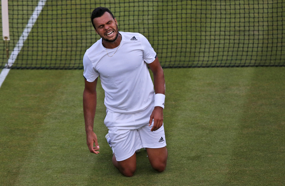 Photo - Jo-Wilfried Tsonga of France falls and grimaces as the light fails as he plays Sam Querrey of U.S. during their match at the All England Lawn Tennis Championships in Wimbledon, London, Wednesday, June 25, 2014. The match was suspended due to bad light at 9 games all in the fifth and final set.(AP Photo/Sang Tan)