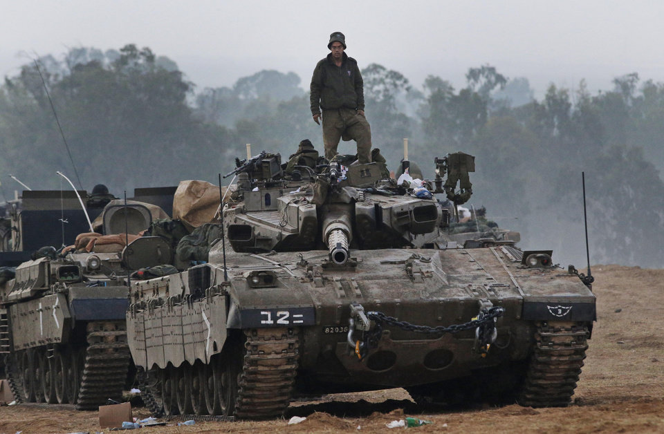 Photo -   An Israeli soldier stands on a tank at a staging area near the Israel Gaza Strip Border, southern Israel, early Tuesday, Nov. 20, 2012. U.N. Secretary-General Ban Ki-moon is urging Israeli forces and Gaza militants to hold their fire, warning that a further escalation of the seven-day-old conflict would endanger the entire region. (AP Photo/Lefteris Pitarakis)