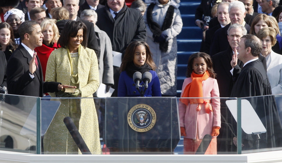 Photo - Barack Obama, left, joined by his wife Michelle, second from left, and daughters Malia, third from left, and Sasha, takes the oath of office from Chief Justice John Roberts to become the 44th president of the United States at the U.S. Capitol in Washington, Tuesday, Jan. 20, 2009.  (AP Photo/Ron Edmonds)