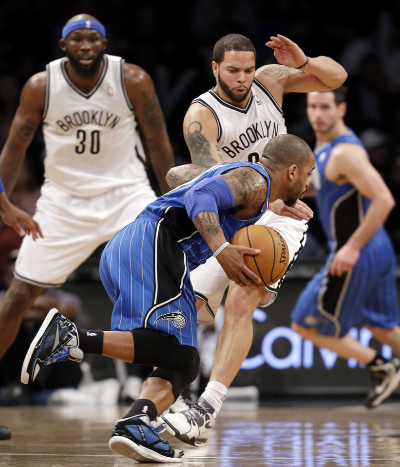 Orlando Magic guard Jameer Nelson (14) drives past Brooklyn Nets forward Reggie Evans (30) and Nets guard Deron Williams (8) in the first half of their NBA basketball game at the Barclays Center, Monday, Jan. 28, 2013 in New York. (AP Photo/Kathy Willens)