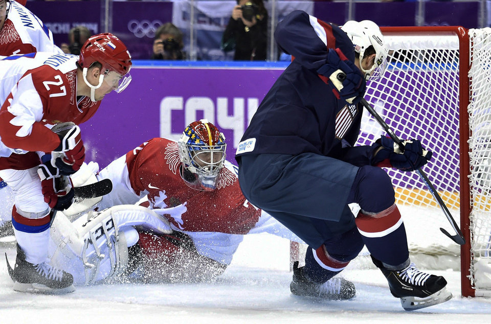 Photo - United States defenseman Cam Fowler, right, scores past Russia goalie Sergei Bobrovski, centre, as Russia forward Alexei Tereshenko, left, looks on during second period preliminary round hockey action at the 2014 Sochi Winter Olympics in Sochi, Russia on Saturday, Feb. 15, 2014. (AP Photo/The Canadian Press, Nathan Denette)