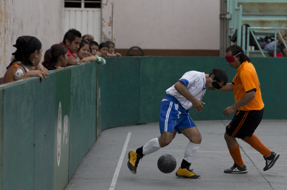 Photo - In this Sunday, June 8, 2014 photo, Italia's Jose Luis Molina, left, 44, controls the ball during the final match against Leones Negros in Mexico City. Molina, a lifelong sportsman who lost his sight completely at age 13, says he feels comfortable playing any position.