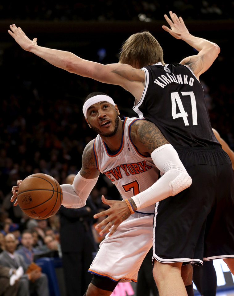 Photo - New York Knicks' Carmelo Anthony, left, looks for the basket past Brooklyn Nets' Andrei Kirilenko during the first half of the NBA basketball game at Madison Square Garden Monday, Jan. 20, 2014, in New York. (AP Photo/Seth Wenig)