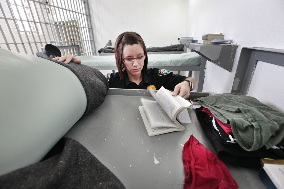 Photo - Midwest City jailer  Jennifer Peek checks an inmates belongings at the city's jail, the largest city jail in Oklahoma. Midwest City officials are working together with the state's mental health agency to start a new jail diversion program. It's similar to drug court or mental health court but on a city level.  David McDaniel - The Oklahoman