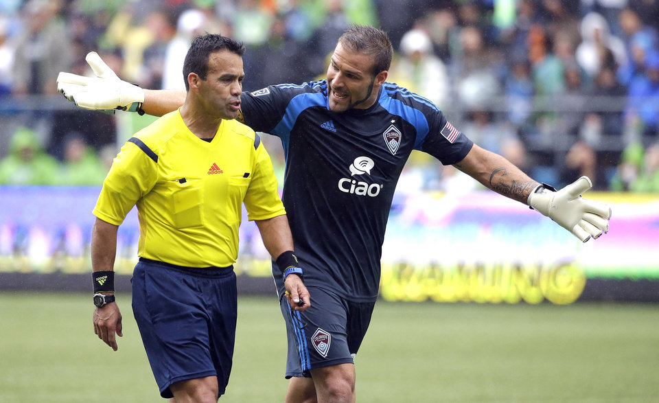 Photo - Colorado Rapids goalkeeper Joe Nasco, right, argues with referee Hilario Grajeda during the second half of an MLS soccer match against the Seattle Sounders, Saturday, Aug. 30, 2014, in Seattle. The Sounders defeated the Rapids 1-0. (AP Photo/Ted S. Warren)