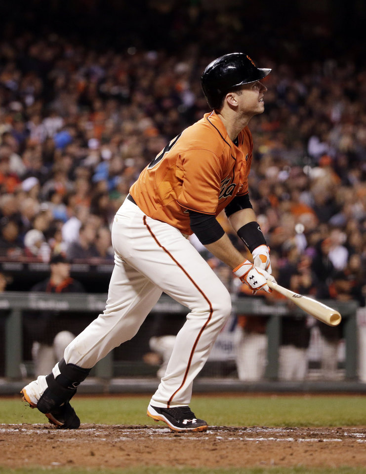 Photo - San Francisco Giants' Buster Posey watches his two-run triple against the Milwaukee Brewers during the fifth inning of a baseball game Friday, Aug. 29, 2014, in San Francisco. (AP Photo/Marcio Jose Sanchez)