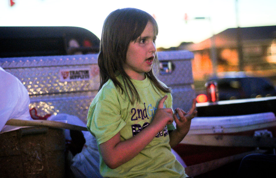 Addyson Roberts, 7, sits on the tailgate of her dad\'s truck and talks about her experience escaping the Plaza Towers Elementary school. Photo by KT King, The Oklahoman