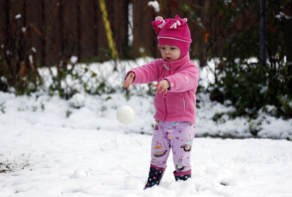 Photo - Molly Cleland, two and a half,  throws her own foam ball in favor to a snowball while playing in the snow in Jackson, Miss., Thursday,  Jan. 17, 2013.  A winter storm system left 2 to 4 inches of snow in parts of central Mississippi before heading east toward Alabama, the National Weather Service said. (AP Photo/Rogelio V. Solis)