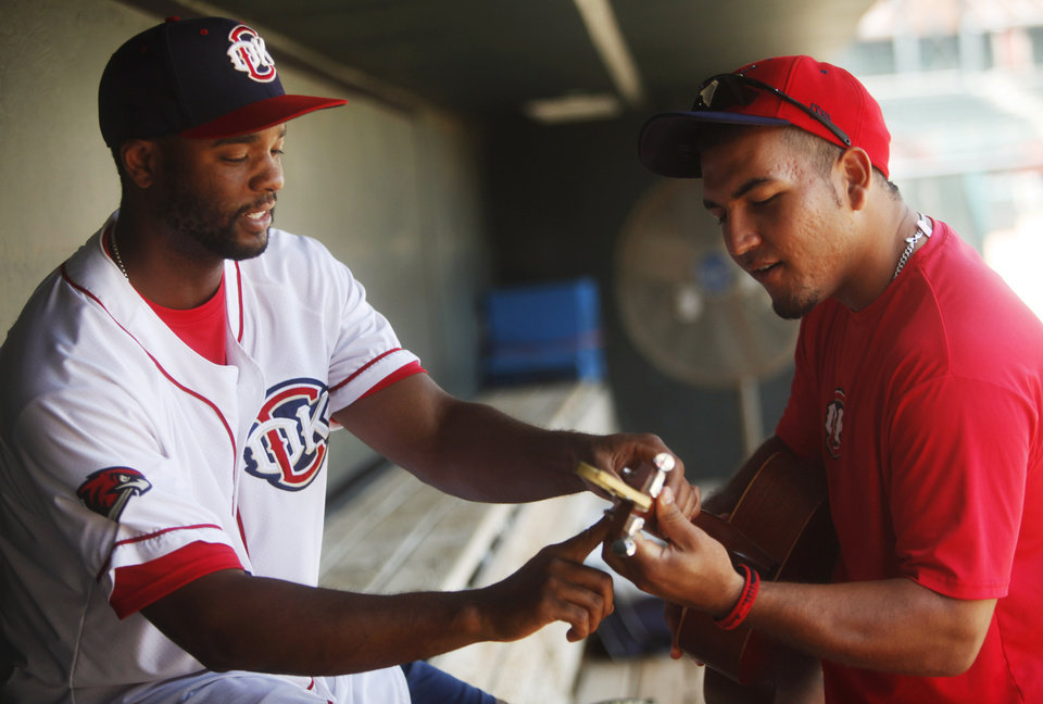 Photo - Redhawks outfielder Austin Wates teaches teammate Carlos Perez simple chord on his guitar in the dugout before practice at the Chickasaw Bricktown Ballpark in Oklahoma City on July 8, 2014. Photo by KT King/The Oklahoman