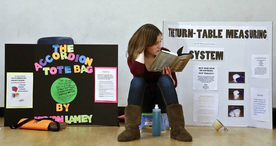 Fifth-grader Julie Dawkins reads a book next to her project during the Deer Creek Middle School science fair on Thursday, March 14, 2013, in Oklahoma City, Okla. Photo by Chris Landsberger, The Oklahoman