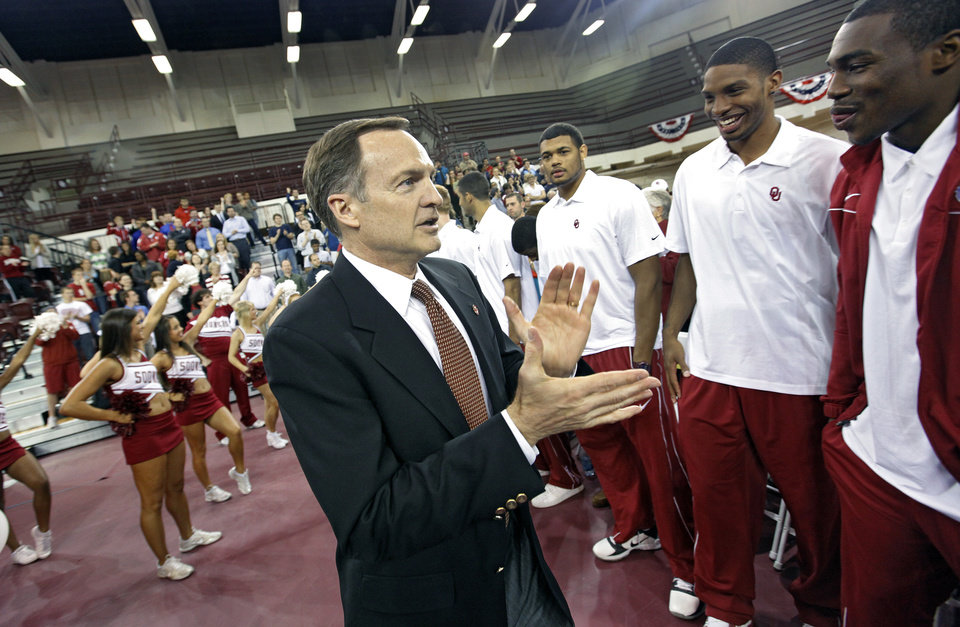 New University of Oklahoma men's basketball coach walks by his new team before being introduced as the new University of Oklahoma men's basketball coach on Monday, April 4, 2011, in Norman, Okla.