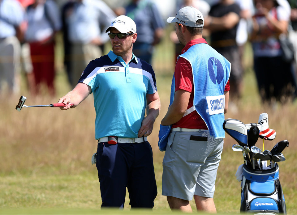 Photo - John Singleton of England talks to his caddie on the 1st green during a practice round ahead of the British Open Golf championship at the Royal Liverpool golf club, Hoylake, England, Tuesday July 15, 2014. The British Open Golf championship starts Thursday July 17. (AP Photo/Scott Heppell)