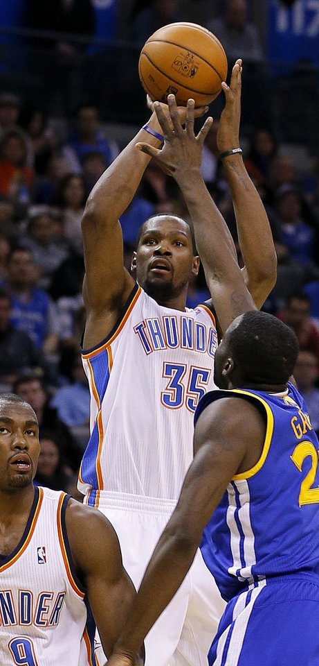 Photo - Oklahoma City's Kevin Durant (35) shoots over Golden State's Draymond Green (23) during an NBA basketball game between the Oklahoma City Thunder and the Golden State Warriors at Chesapeake Energy Arena in Oklahoma City, Saturday, Jan. 18, 2014. Oklahoma City won 127-121. Photo by Bryan Terry, The Oklahoman