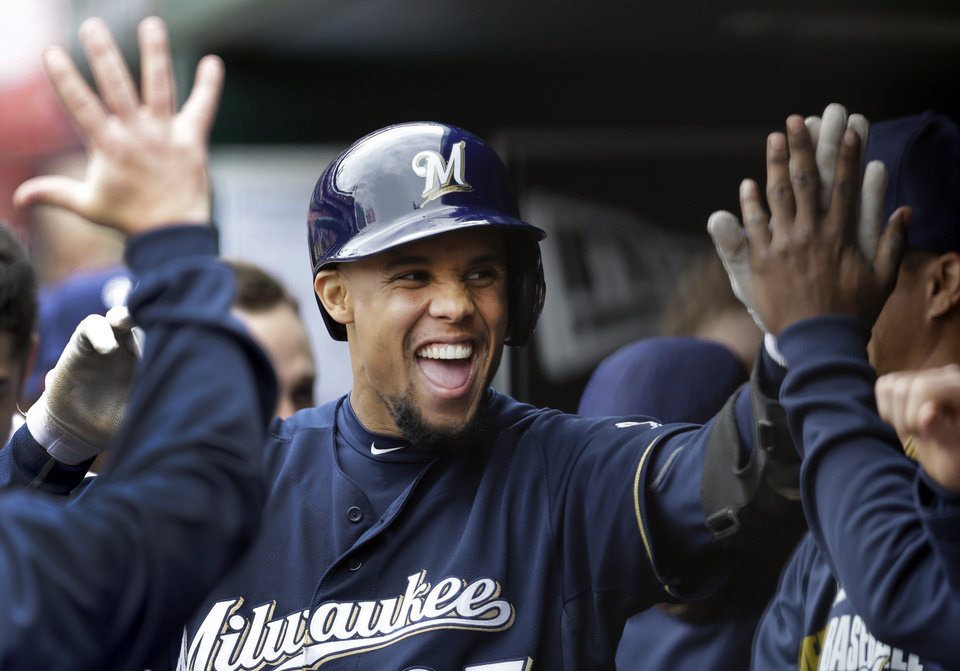 Photo - Milwaukee Brewers' Carlos Gomez is congratulated by teammates after hitting a solo home run during the third inning of a baseball game against the St. Louis Cardinals Wednesday, April 30, 2014, in St. Louis. (AP Photo/Jeff Roberson)
