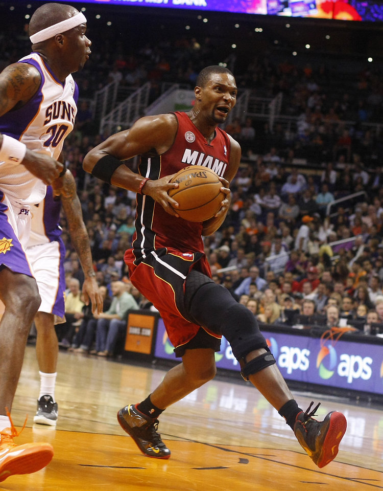 Miami Heat center Chris Bosh (1) drives on Phoenix Suns center Jermaine O'Neal (20) in the second quarter during an NBA basketball game on Saturday, Nov. 17, 2012, in Phoenix. (Rick Scuteri/AP Photos)