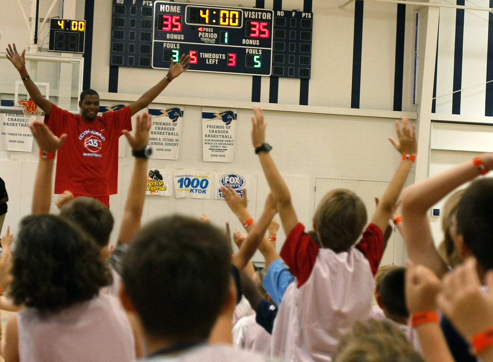 Photo - The participants of the Kevin Durant Basketball Camp cheer with Kevin Durant after he makes a half-court behind-the-back shot. Kevin Durant held a basketball camp Wednesday, June 30, 2010, at Heritage Hall in Oklahoma City. Photo by Mitchell Alcala, The Oklahoman.