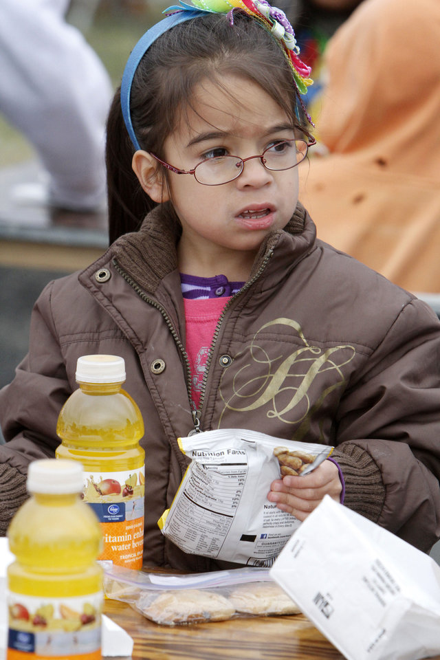 Photo - Six-year-old Adriana Marota unpacks a free lunch at last year's ONE DAY event. Archive photo by Paul Hellstern,  The Oklahoman.  PAUL HELLSTERN