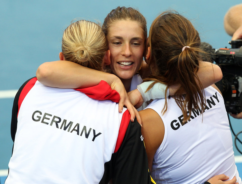Photo - Andrea Petkovic, center, of Germany celebrates with her teammates after winning 6-1, 7-6, in her semifinal match against Samantha Stosur of Australia during the Fed Cup semifinals between Australia and Germany in Brisbane, Australia, Saturday, April 19, 2014. (AP Photo/Tertius Pickard)